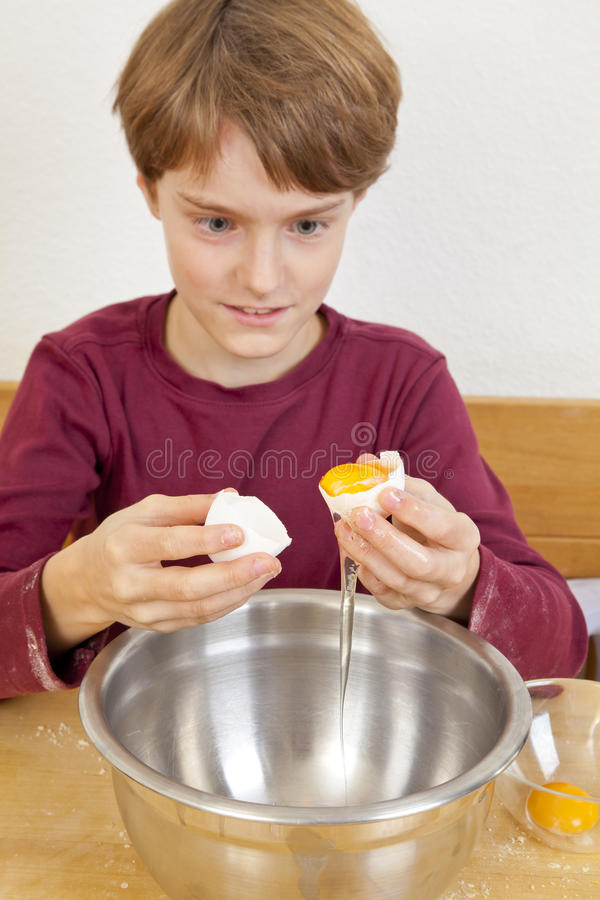 Boy separating egg white from egg yolk. An eleven years old boy sitting in the kitchen in front of a bowl and separating egg white from egg yolk royalty free stock image