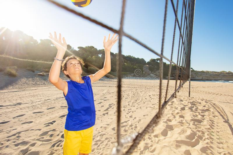 Boy serving the ball during beach volleyball game. Portrait of teenage boy in uniform serving the ball during beach volleyball game at sunny day royalty free stock photos