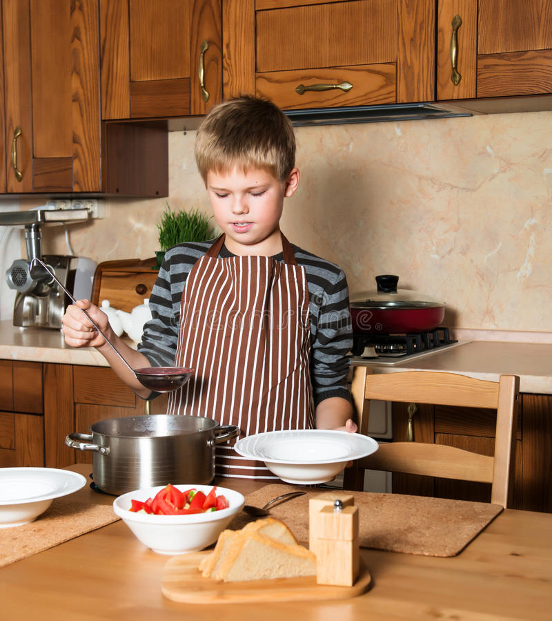 Boy serving Borshch, traditional Russian and Ukrainian soup. Pouring soup into a plate with ladle from pan in kitchen. Child serving Borshch, traditional royalty free stock photo