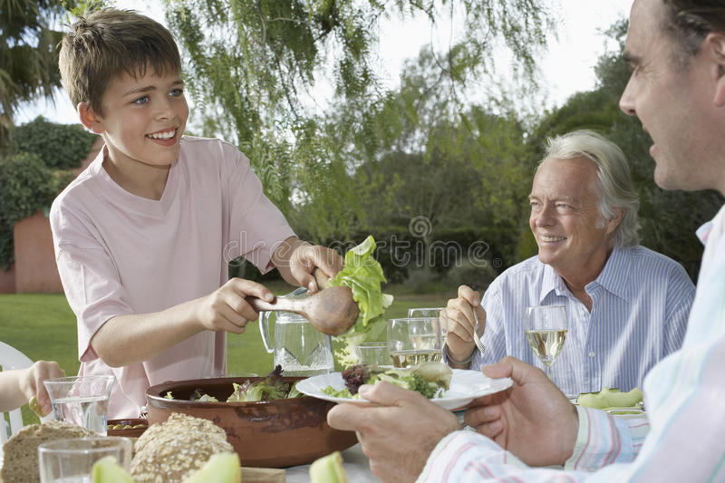Boy Serving Father At Outdoor Table stock image