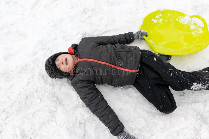 A boy of seven years old lying on the snow and holding a green plastic sled in his hand. Concept of winter activities, recreation. And children`s entertainment stock photography