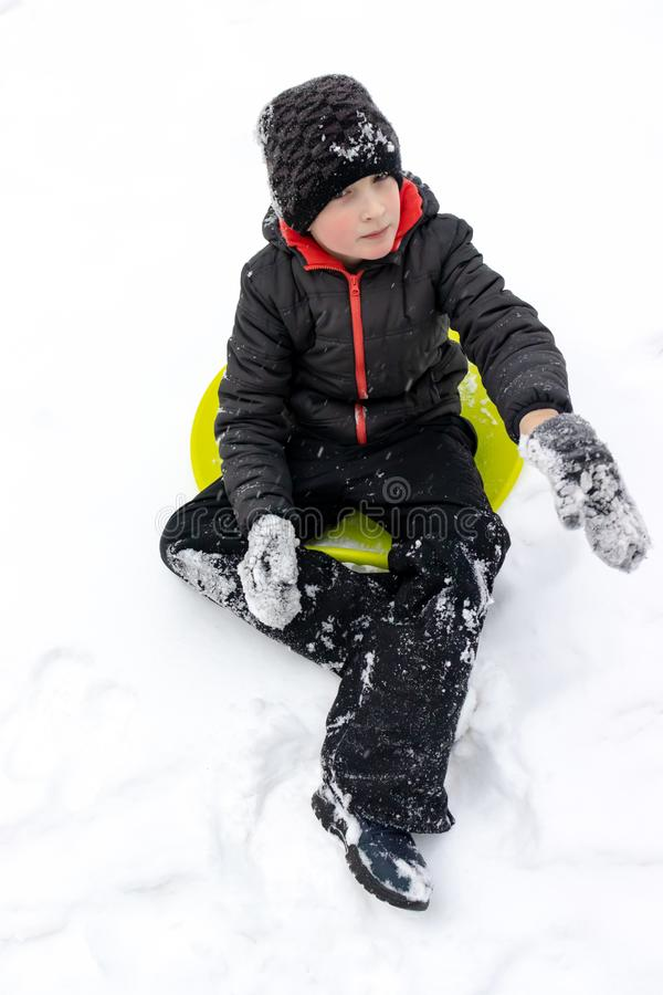 A boy of seven years old sitting on a green plastic saucer sled ready to ride a slide. Concept of winter activities, recreation. And children`s entertainment royalty free stock image