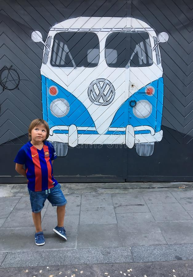 A boy in the shape of a Barcelona FC near a graffiti painting of a Volkswagen bus painted on a wall. stock image
