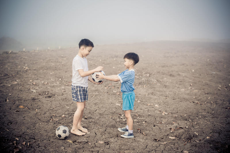 Boy share football. Little asian boy give brand new football to another boy royalty free stock photography