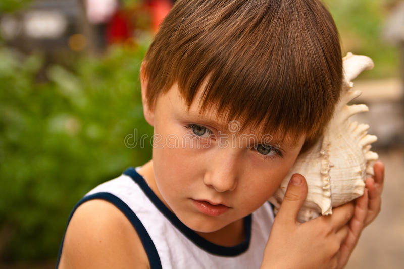 Boy with a shell stock photo