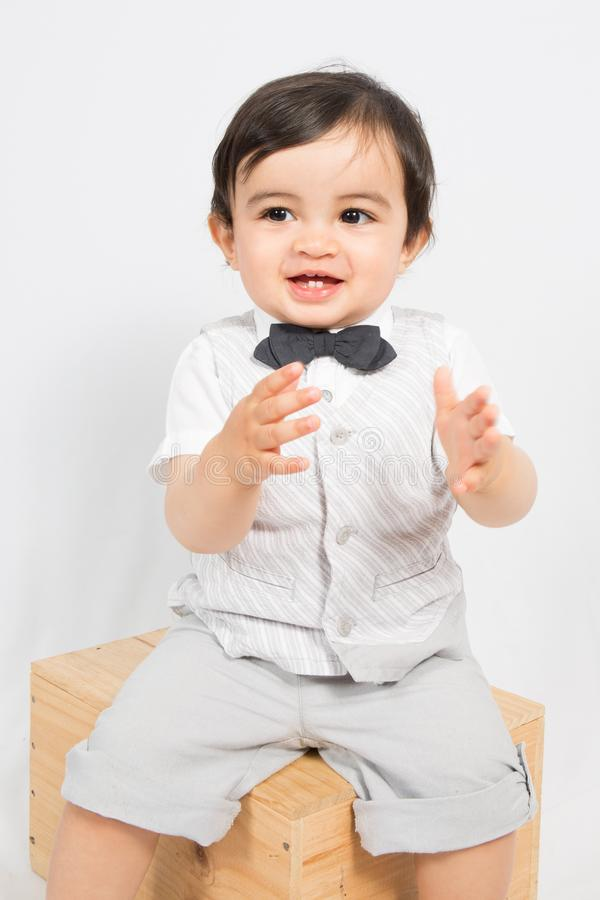 Boy in a shirt and bow tie sit on box ready to applaud. A boy in a shirt and bow tie sit on box ready to applaud royalty free stock photo