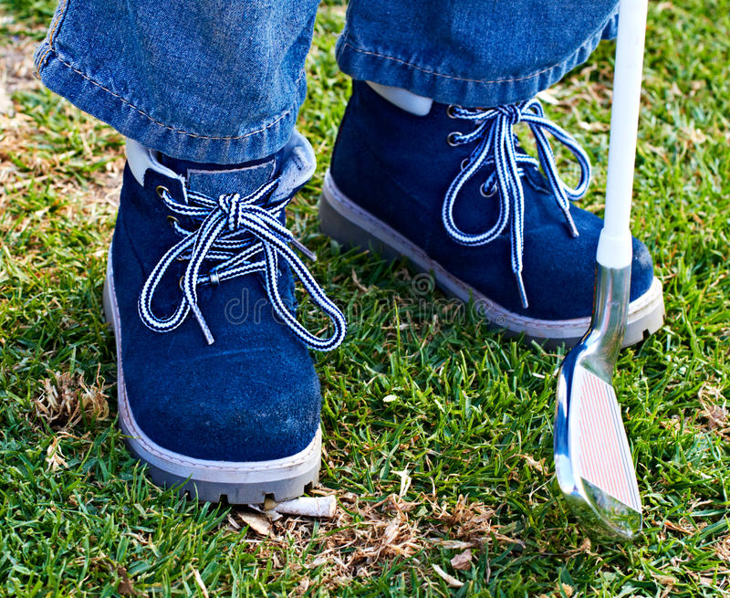 Boy shoes and golf club on grass royalty free stock photo