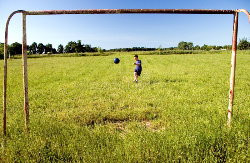 Boy shooting at goal. A boy practicing his football skills, shooting at empty goal, the ball in the mid air. MORE SPORT IMAGES royalty free stock photo