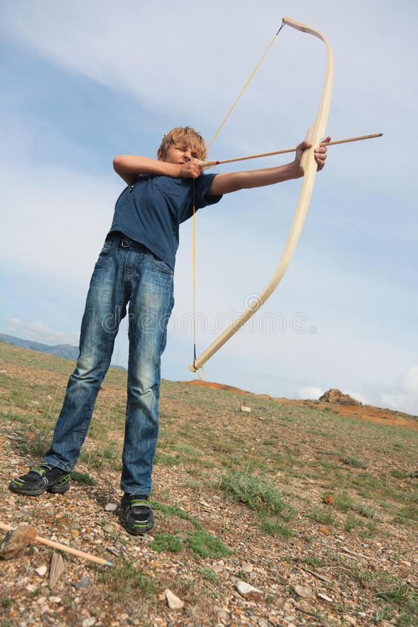 Boy shoots a bow at a target stock photos