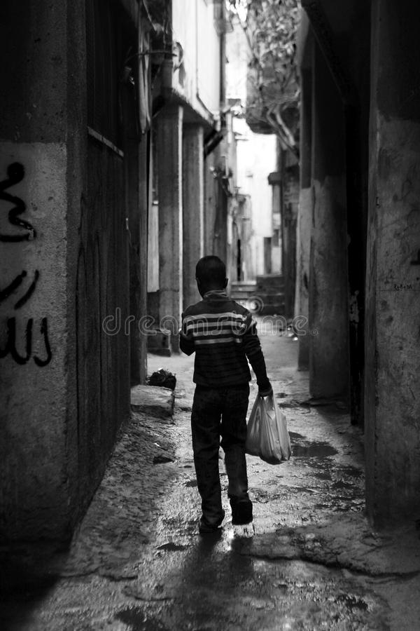 Boy with shopping bag in the street of Ramallah. Refugee camp Aida royalty free stock photo