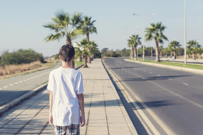 A boy in  a shorts and a T-shirt goes on the sidewalk along the road in the resort town. A boy in  a shorts and a T-shirt goes on the sidewalk along the road in stock photography