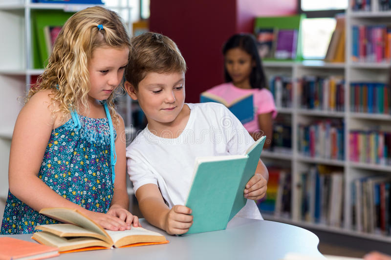 Boy showing book to classmate. Cute boy showing book to female classmate in library royalty free stock photography
