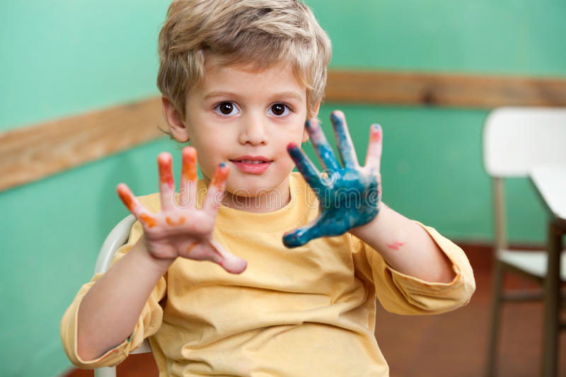 Boy Showing Colored Palms In Art Class. Portrait of little boy showing colored palms in art class royalty free stock images