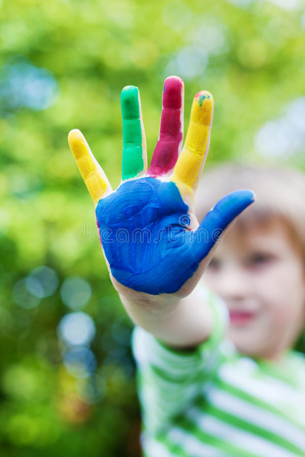 Boy showing his colorful painted hand in the garden royalty free stock image