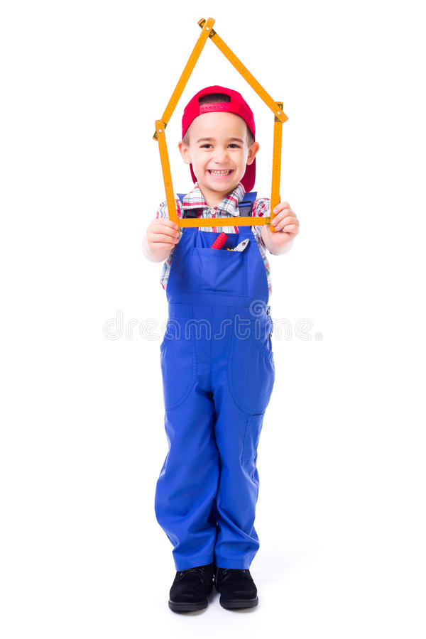 Boy showing house made of measuring ruler stock photo