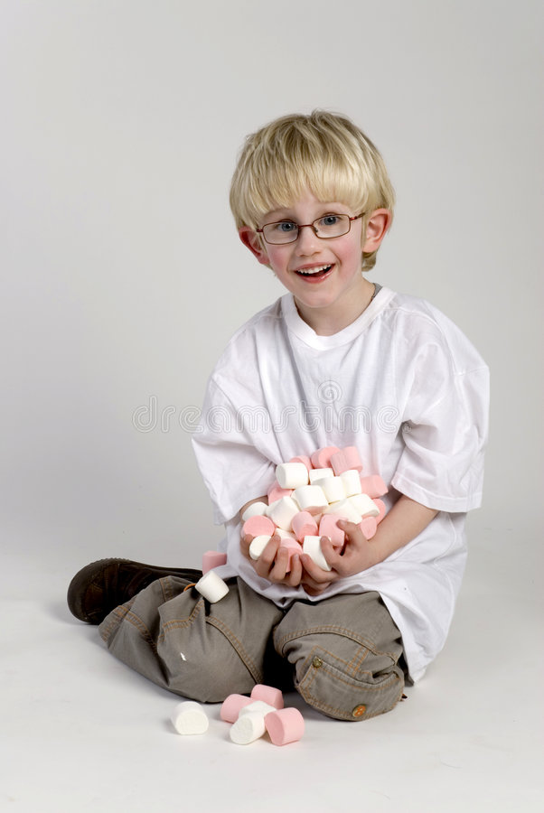 Boy is showing lots of candy. Small boy is sitting on the ground with hands full of candy stock photo