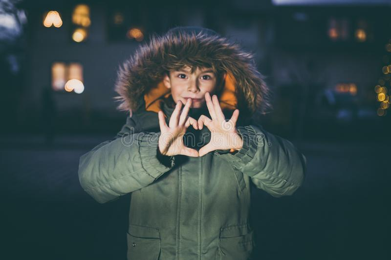 Boy showing love heart with hands outdoors with christmas lights stock photos