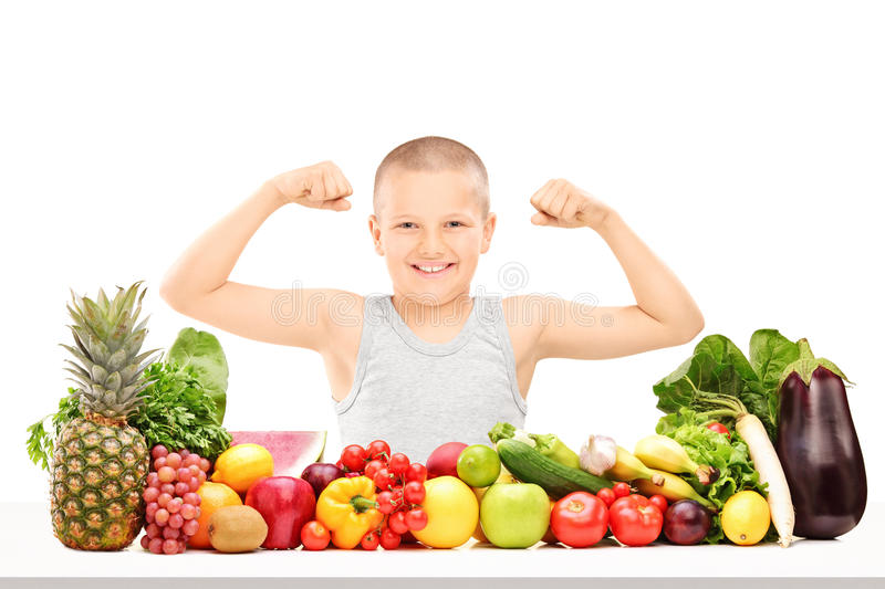 Boy showing muscles behind pile of vegetables. Boy showing muscles behind pile of fruits and vegetables isolated on white background stock photography