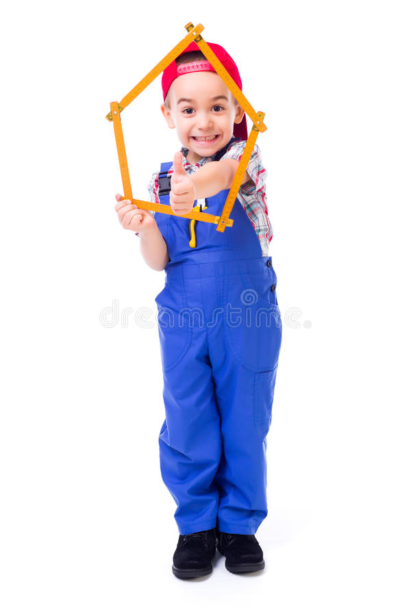 Boy showing thumbs up through house made of measuring ruler stock photos