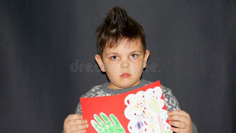 The boy shows his humane work, the boy looks at the camera. Boy with modern hairstyle, modern boy hairstyle, humane work, black boy, little boy. human face stock photo