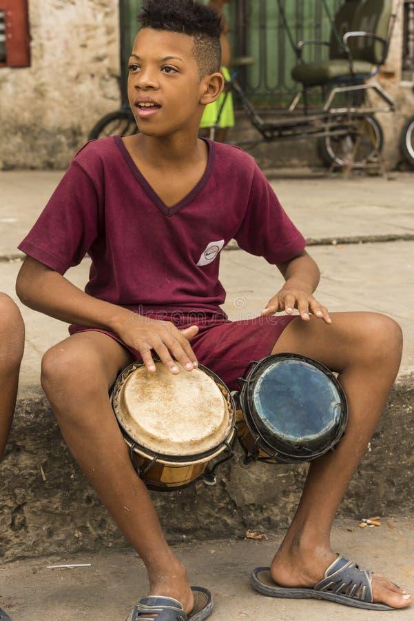 Boy on sidewalk playing bongos Havana stock images