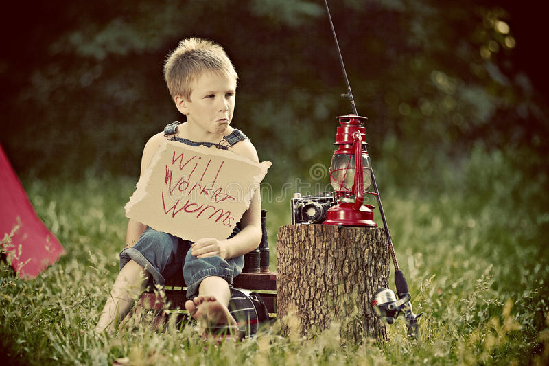 Boy with Sign. Little boy with fishing pole holding a sign that says Will Work for Worms royalty free stock photos