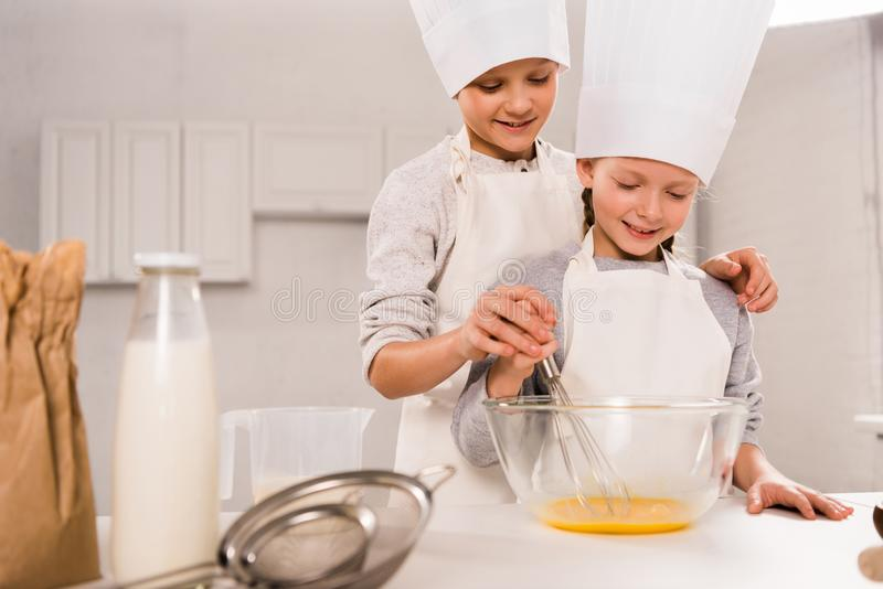Boy with sister in chef hats whisking eggs in bowl at table. In kitchen stock photography