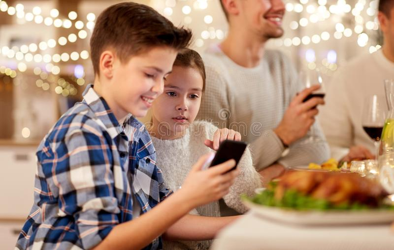 Boy with sister using smartphone at family dinner royalty free stock photo