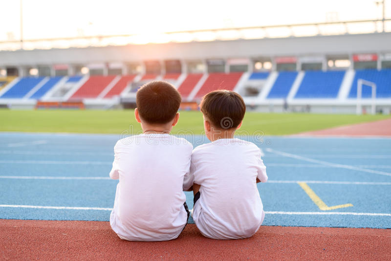 Boy sit on the running track. Two asian boy sit beside the blue running track and look to the stadium and sunset royalty free stock images