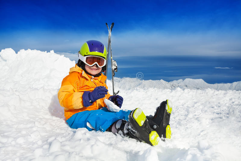 Boy sit in snow with ski mask and helmet royalty free stock photography