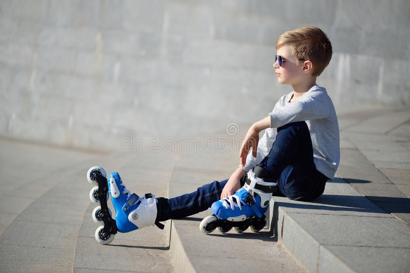 Boy siting with inline roller skates at outdoor skate park stock images