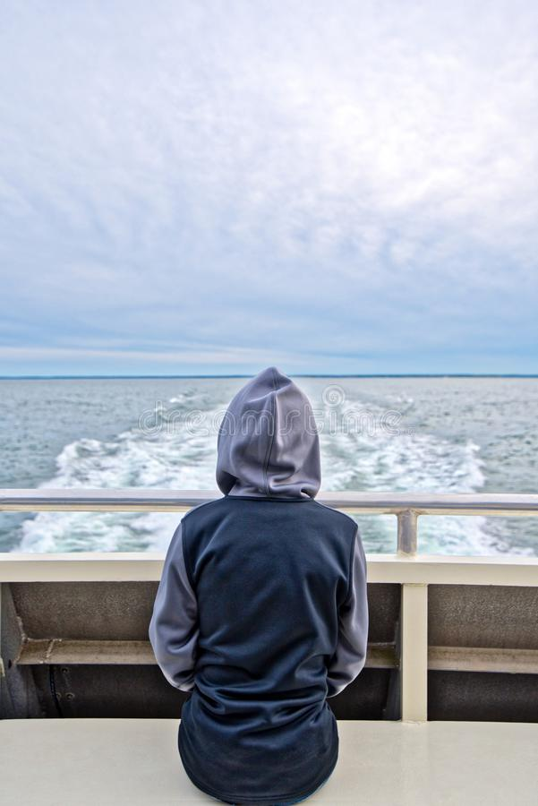 A boy sits at the back of a boat and watches the Island of Nantucket disappear from the horizon. A young boy sits on a the back of a boat on a chilly evening as stock photo