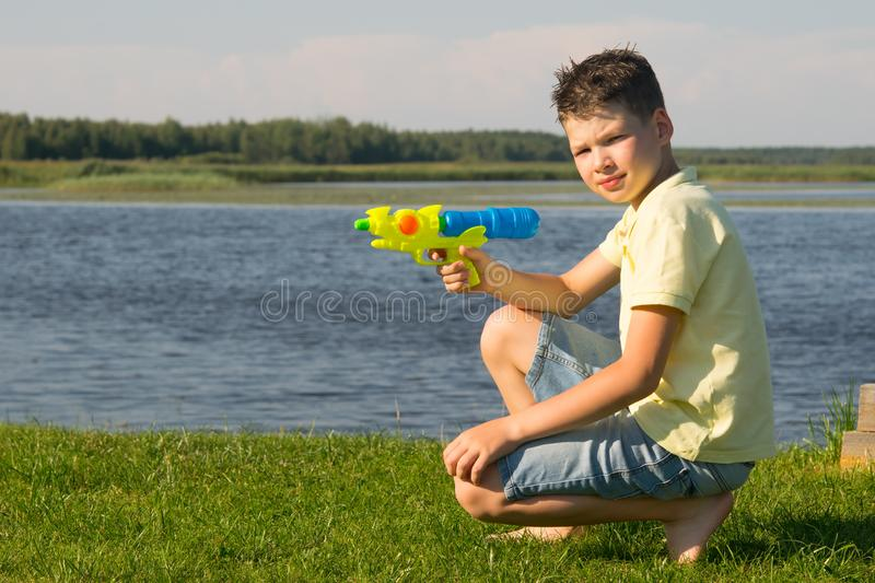 The boy sits on the green grass and plays with a water gun, against a beautiful landscape, close-up royalty free stock images