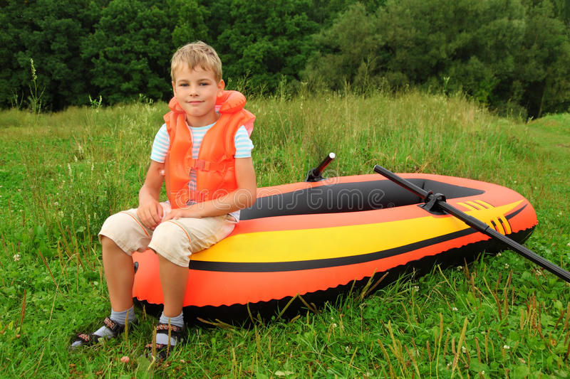 Boy sits on an inflatable boat on lawn. Summer stock photos