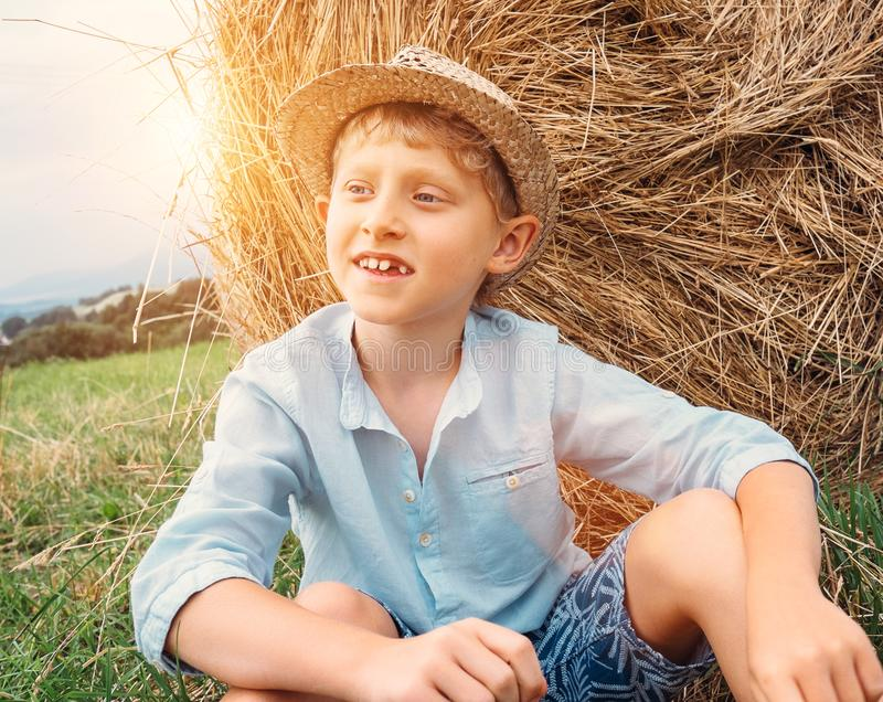 Boy sits near big haystack on the field royalty free stock photo