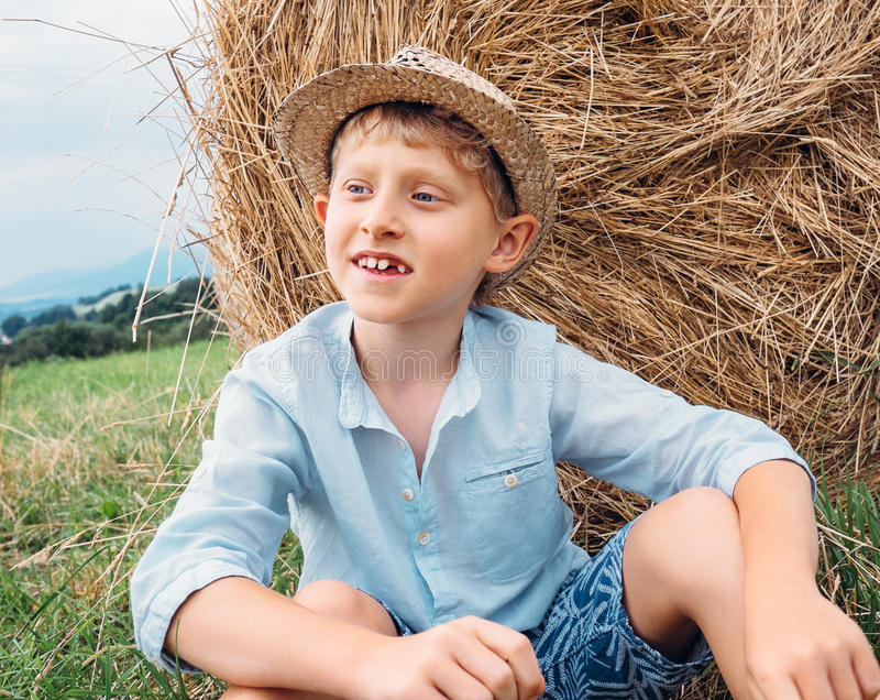 Boy sits near big haystack on the field stock images