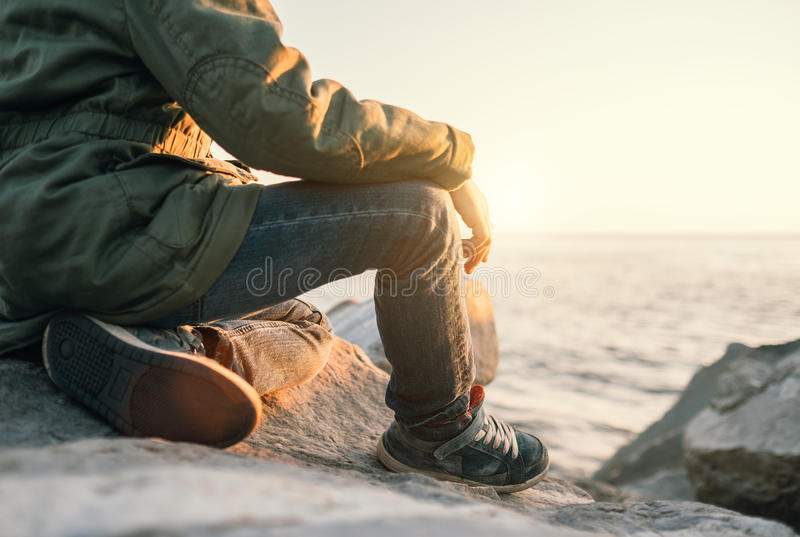 Boy sits near the sea at sunset time. Close up legs image stock photo