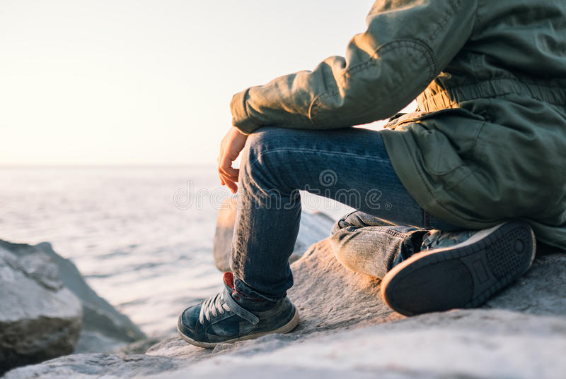 Boy sits near the sea at sunset time. Close up legs image royalty free stock photos