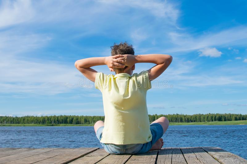 The boy sits on the pier, doing yoga, against the blue sky and the lake royalty free stock image