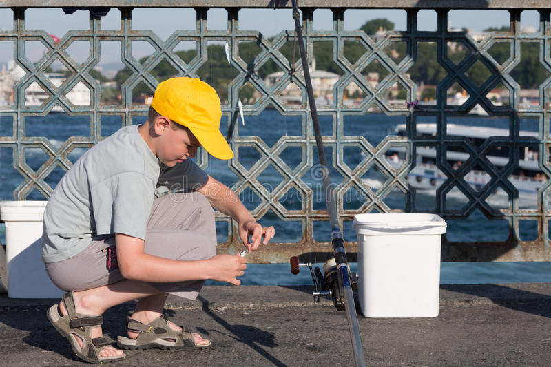 The boy sits and puts bait on hook. The boy in yellow cap sits and puts the bait on the hook royalty free stock photography