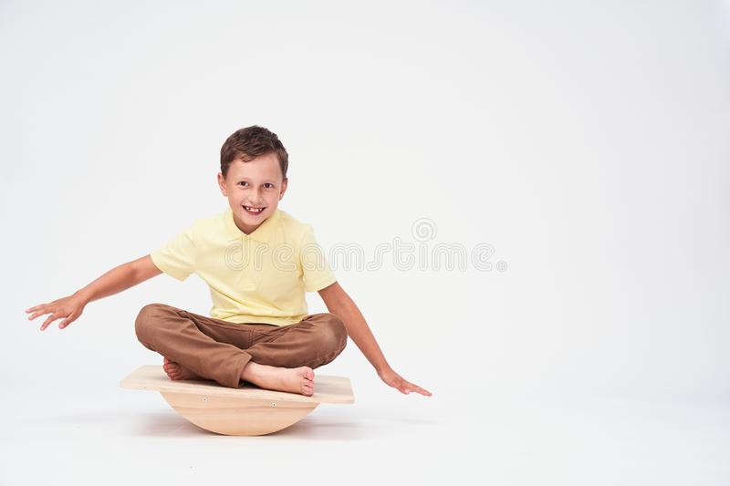 Baby boy sits on a special simulator for training the vestibular apparatus..balance exercise balancing. Boy sits on a special simulator for training the royalty free stock image