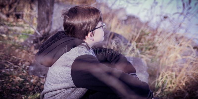 A Boy Sitting on the Bank Daydreaming royalty free stock photo
