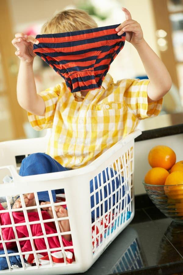 Download Boy Sitting In Basket Sorting Laundry Stock Image - Image: 27704299