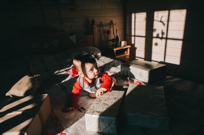Boy sitting on the bed considering gifts royalty free stock images