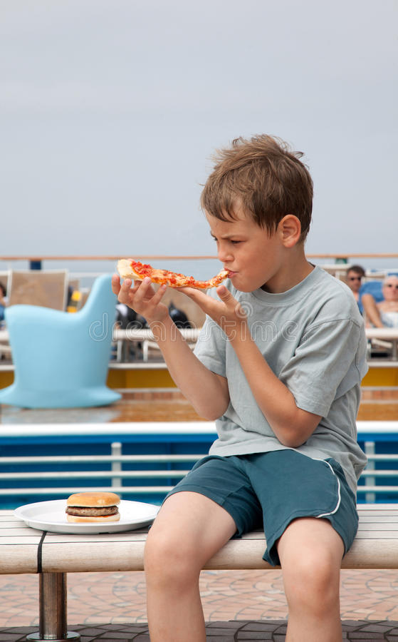 Boy sitting on bench eating pizza royalty free stock image