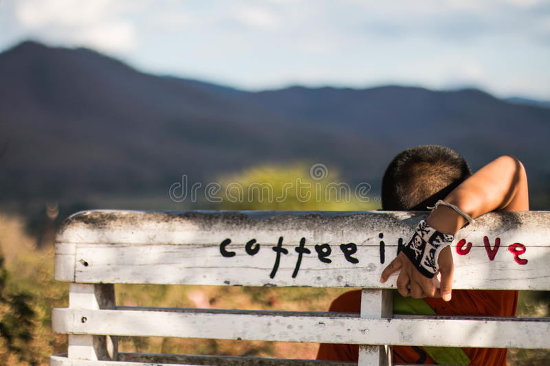 Boy sitting on the bench with mountain view royalty free stock image