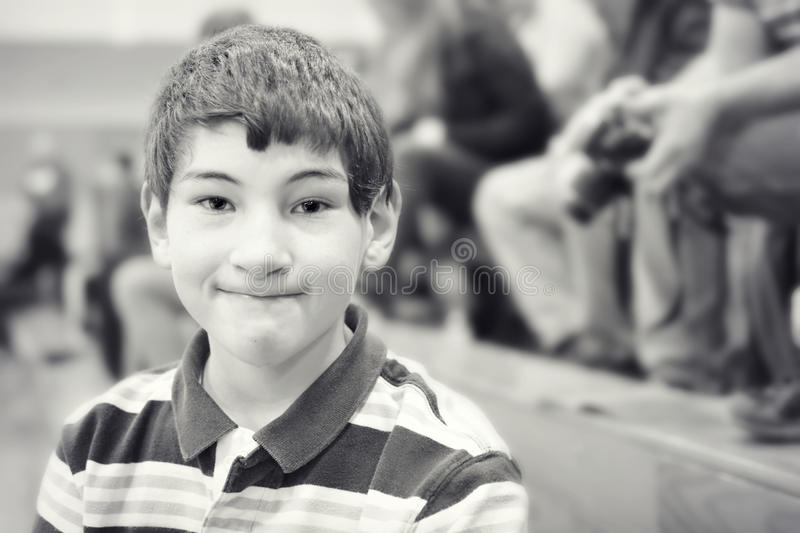 Boy Sitting in Bleachers. A monochrome photo of an elementary aged boy sitting in the bleachers royalty free stock photo