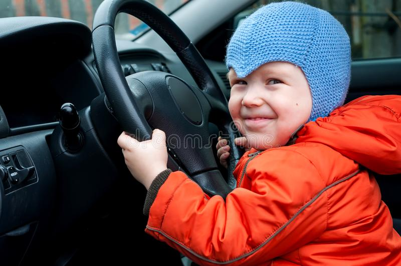 Boy sitting in the car as the driver. Holds the steering wheel car royalty free stock images