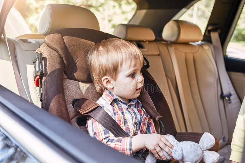 Boy sitting in a car in safety chair. Family road trip stock images