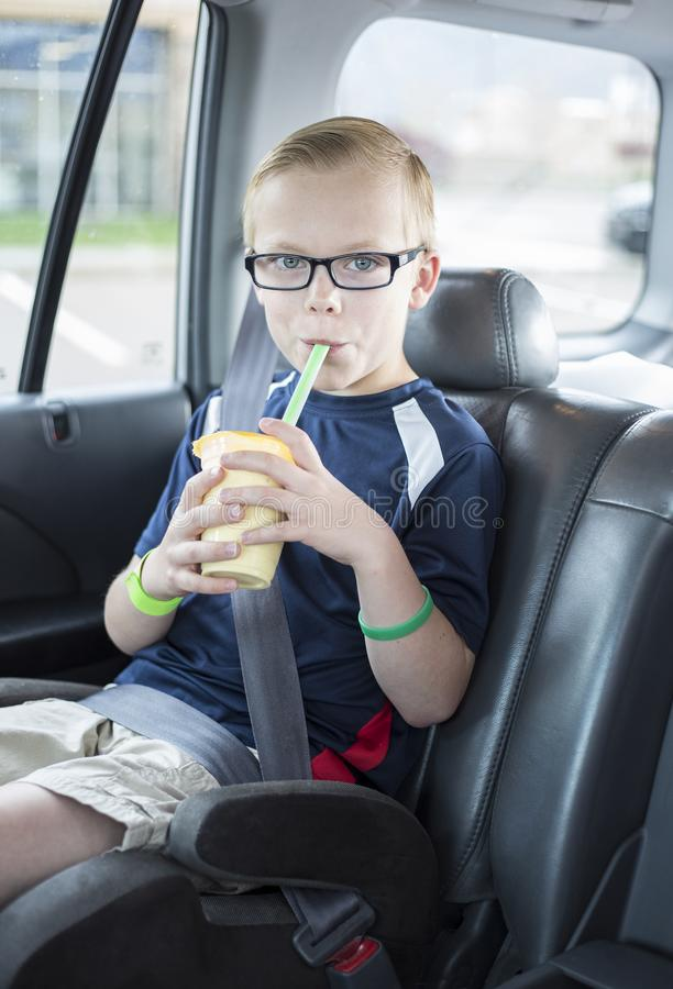 Boy sitting in a car seat drinking a smoothie on a long car ride. Cute boy sitting in a booster seat on a long car ride drinking a smoothie while safely strapped royalty free stock images